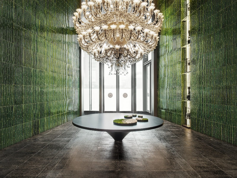 Large chandelier in front of green wall surfaces in lobby