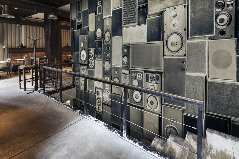 Grey wall mural reflects sound speakers on the wall