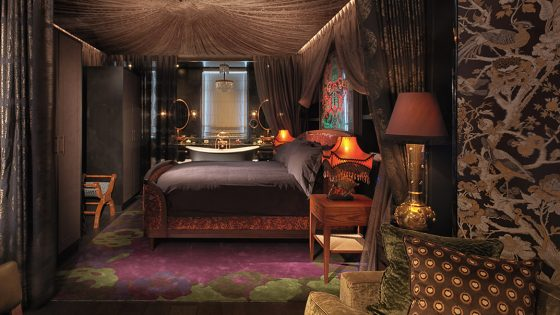 Dark-toned room with high ceilings mixes plush velvet and low lighting