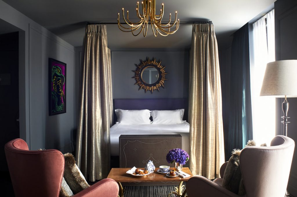 Guestroom with statement circular mirror on the wall