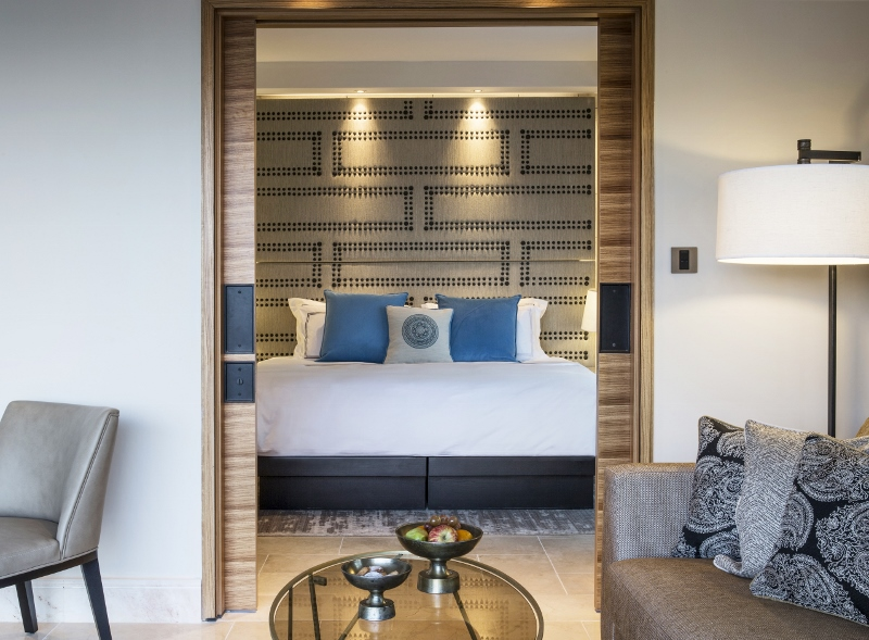 Large guestroom with studded headboard and dark, natural tones