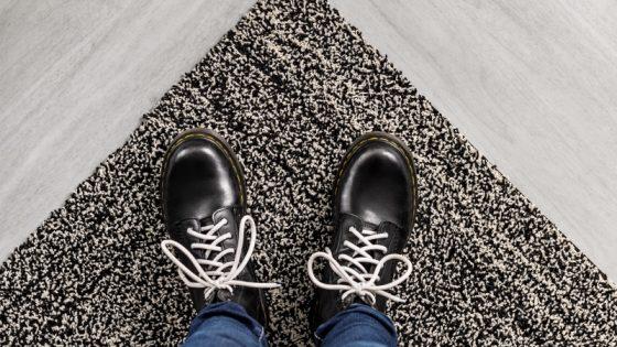 Men;s feet on the edge of a carpet