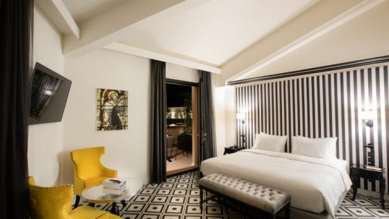 Monochrome interiors in the guestroom with accents of mustard yellow