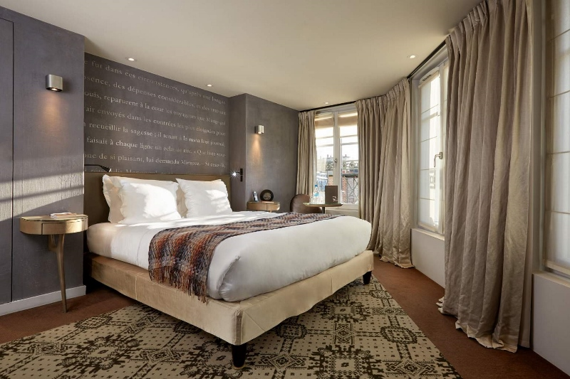 Cosy guestroom with clear words written above the bed on the grey headboard. The room is modern and designed specifically for writing lovers