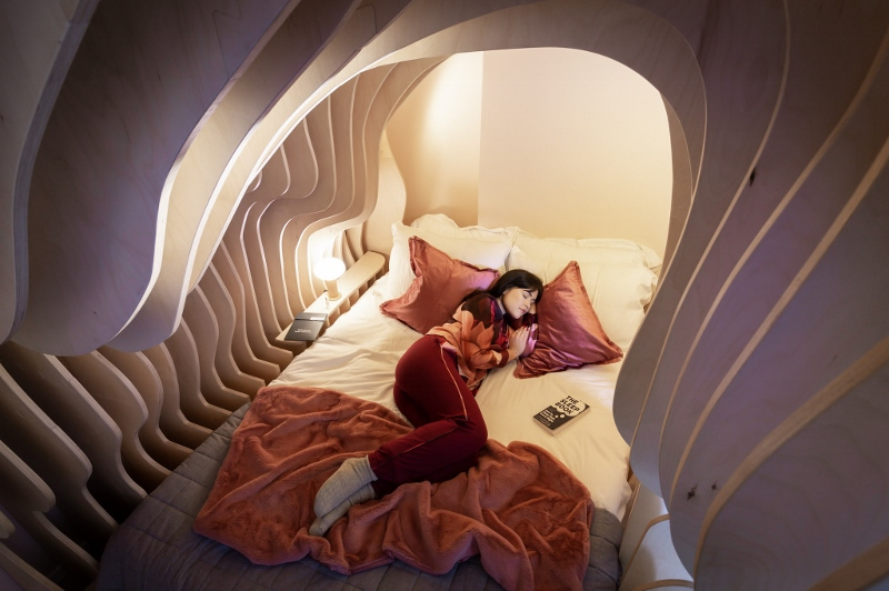 Girl sleeping on a bed that is surrounded by a structure that is designed to resemble the womb