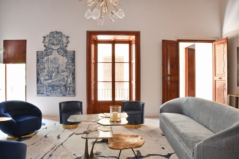 Palatial interiors in palma with soft grey curved sofa and wooden door frames