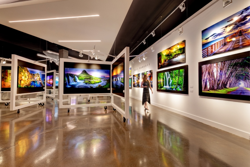 The large, modern art gallery includes landscape photos on the walls and around the room