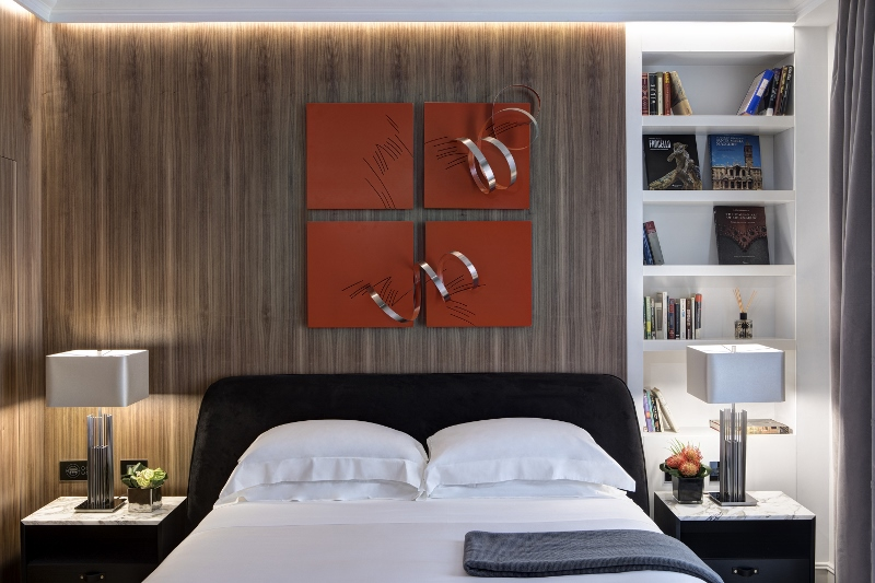 Modern bedroom with maroon art above white-linen bed and a white bookshelf to the right