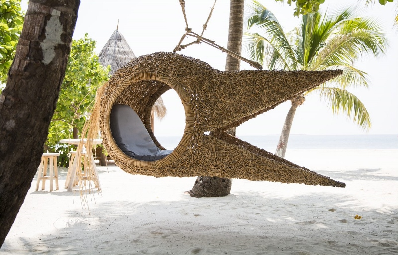 A beak-like seat hangs on the beach/bar area of the hotel