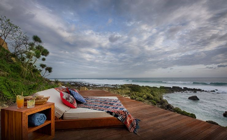 Exterior shot of large bed on decking overlooking majestic sea views