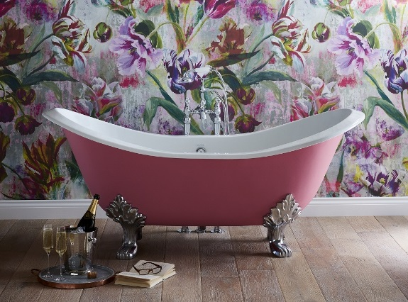 Pink bath in front of a floral wallpaper