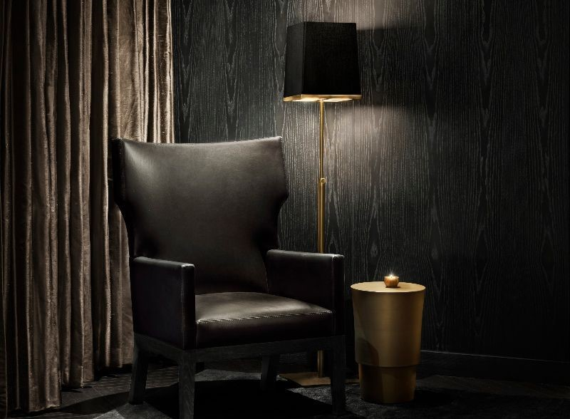black armchair infront of black wallcoverings