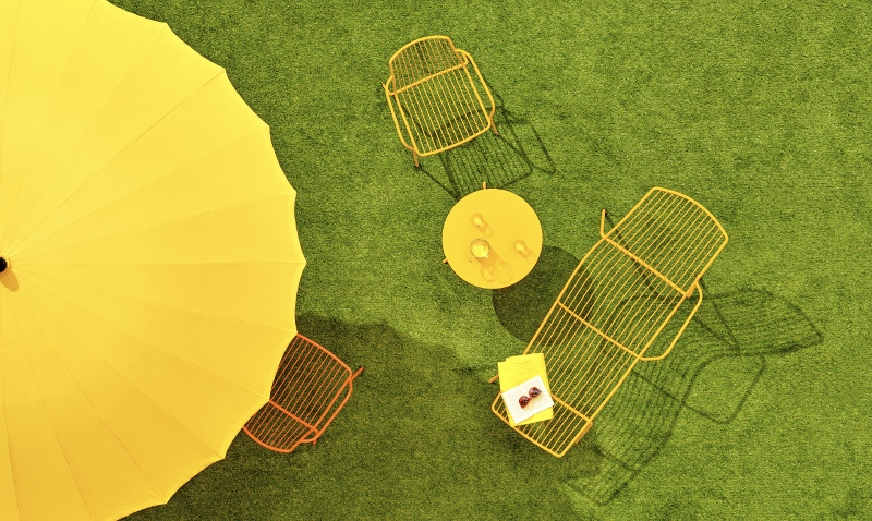 Green grass, yellow umbrella and chairs