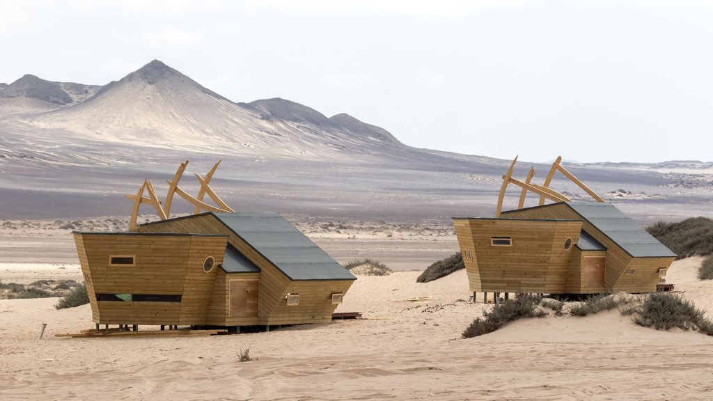 Image of one of the lodges blending into the surroundings of sand dunes.