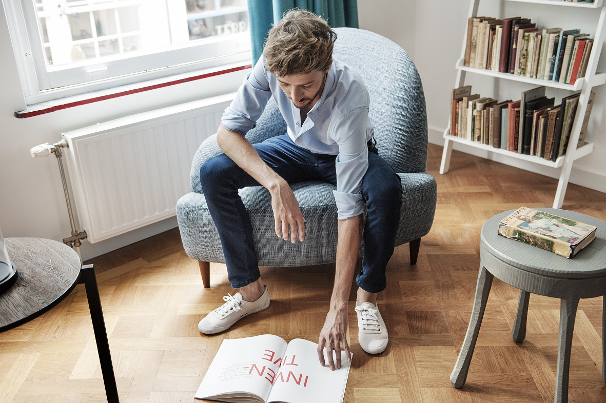 Image of the designer flicking through a book on the floor