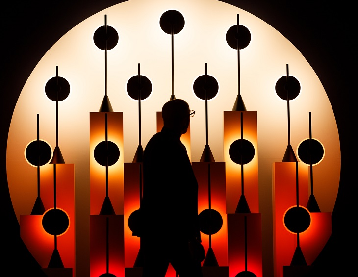 Man walking in front of light installation