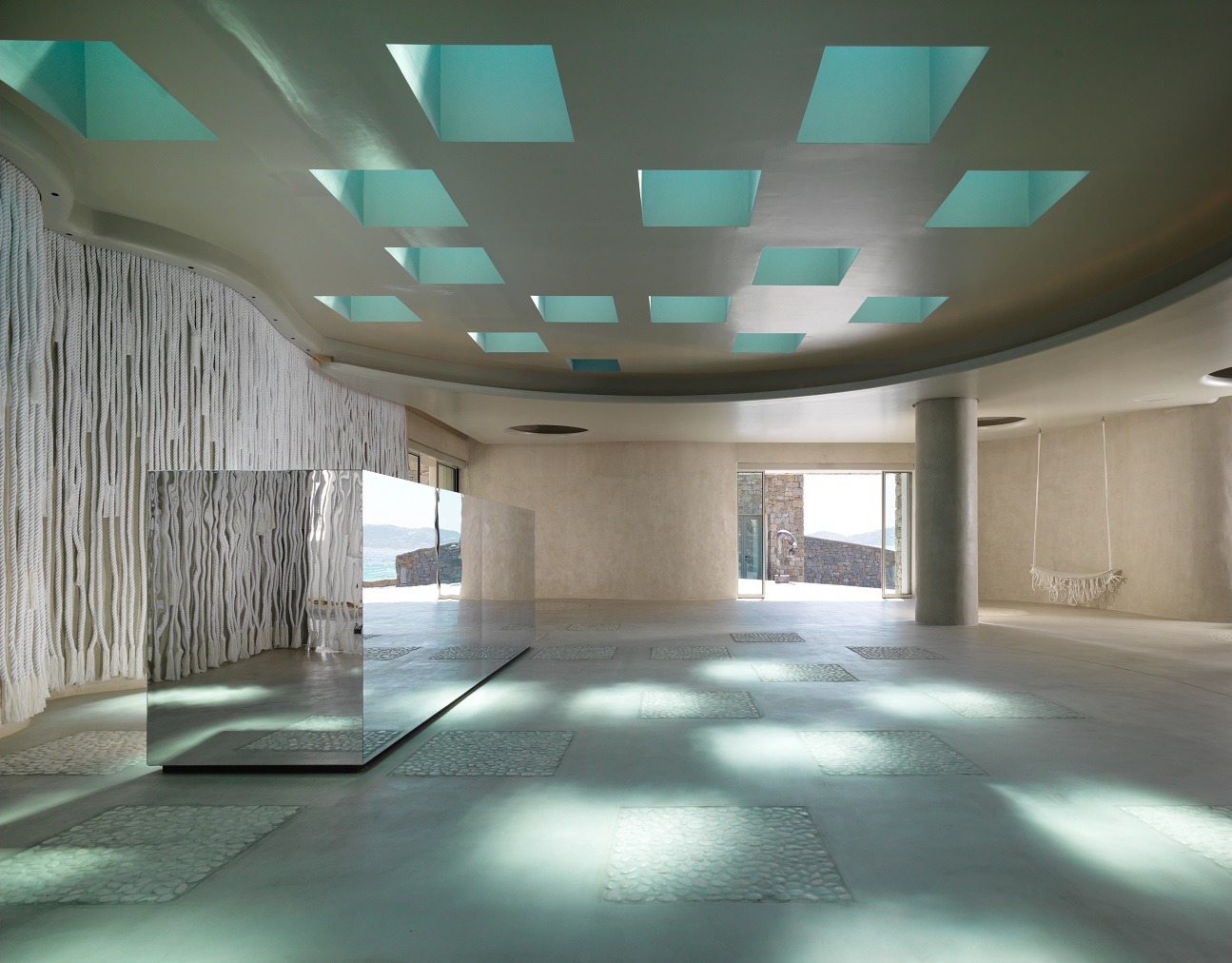 Minimalist check-in desk with colours of turquoise in ceiling and reflection on floor
