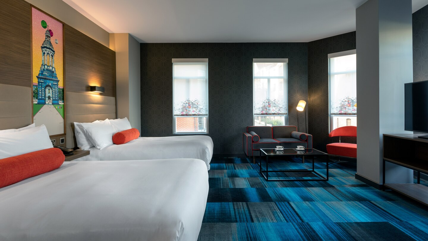 Vibrant blue carpets in large guestroom