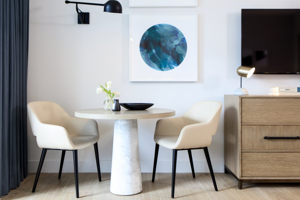 Close up of modern furniture above abstract blue art piece in white suite