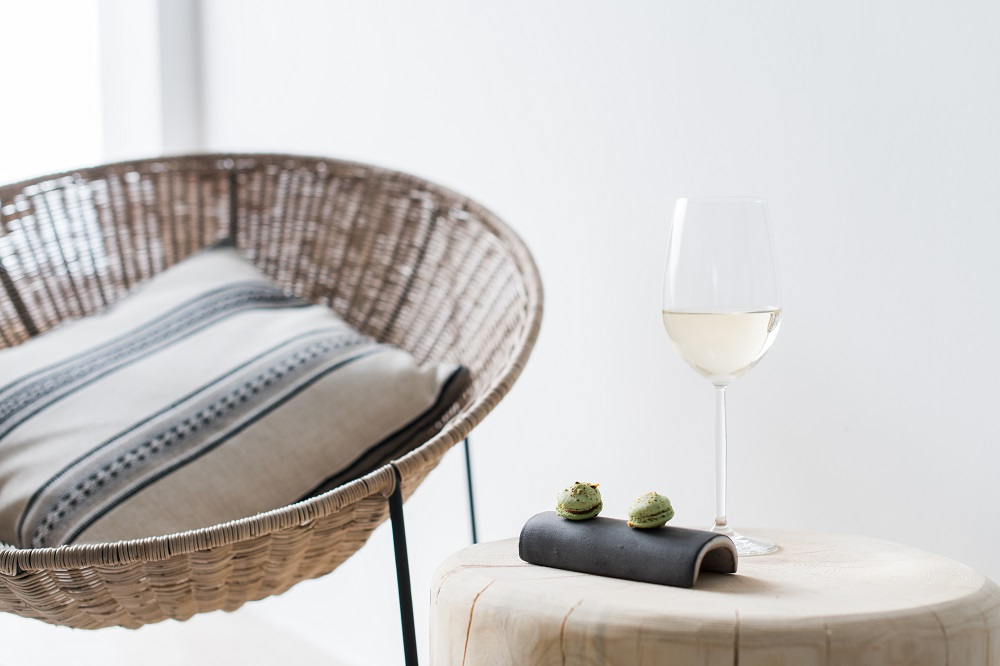 Close up of woven chair and a glass of white wine