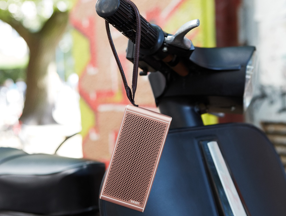 Image of portable speaker (rose gold) on handlebars of bike