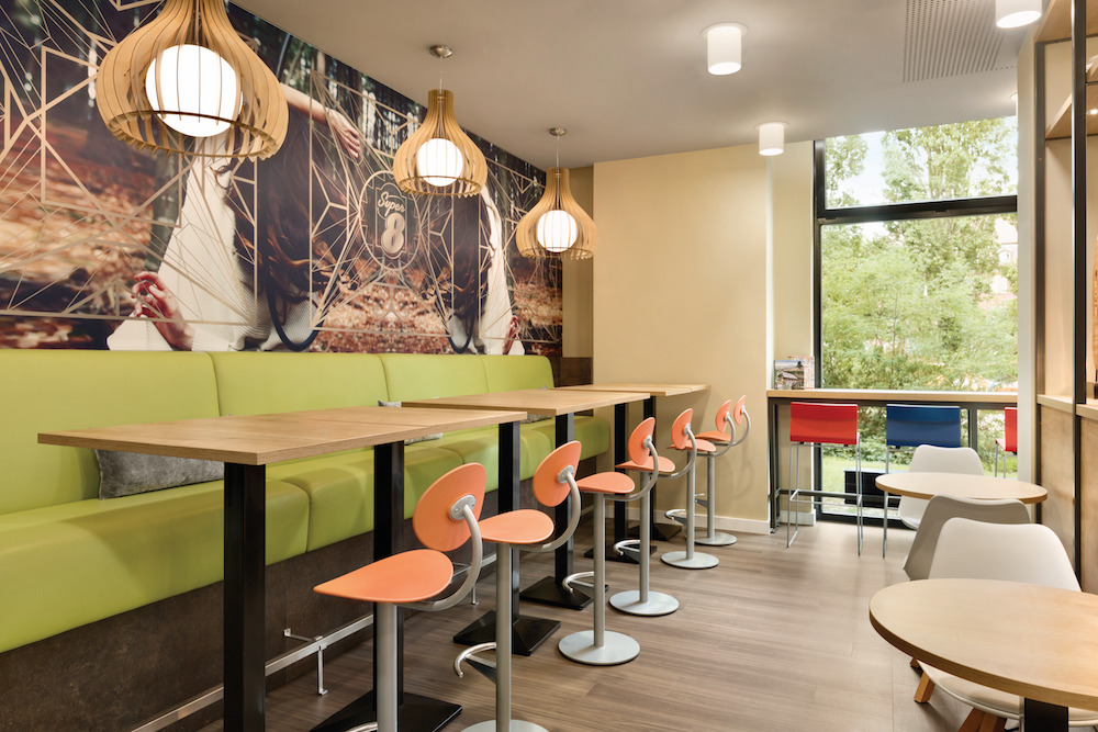 Green bench and orange chairs in modern f&B area