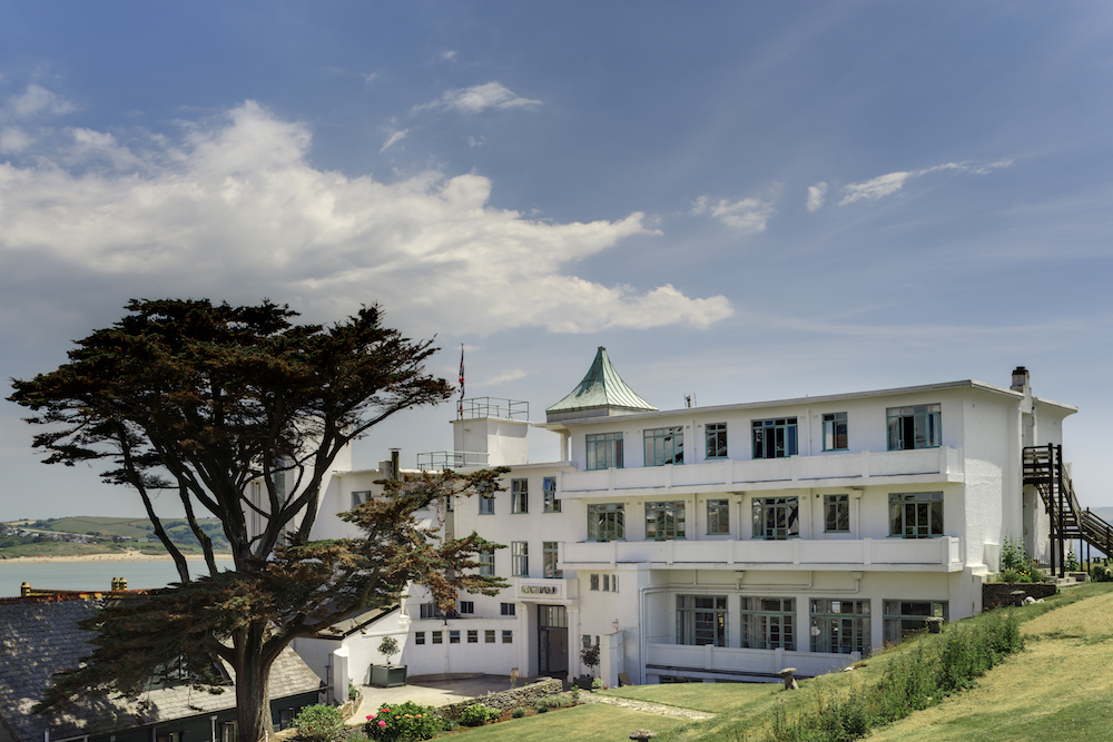 Exterior shot of the hotel with blue sky and green lawns