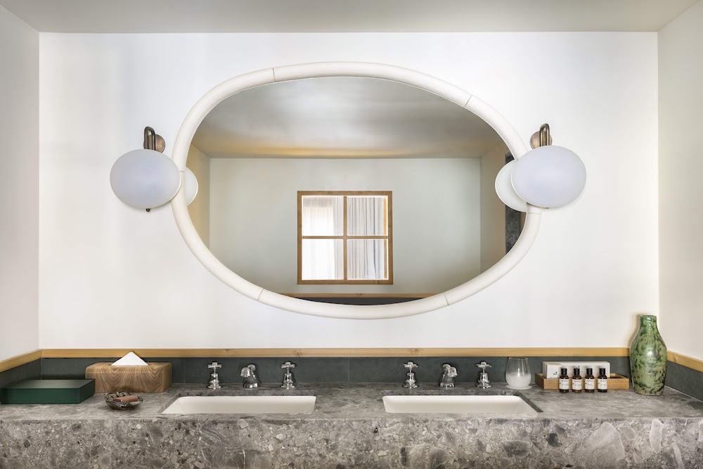 marble bathroom reflecting the chalet window in the oval mirror