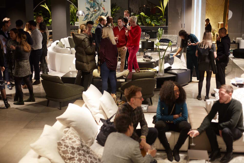 people sitting on sofas and standing, networking in the Minotti London showroom