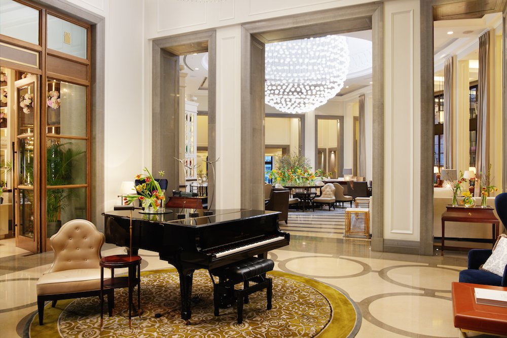 Spacious and luxury hotel lobby. Grand piano in the centre, and a large chandelier in the background