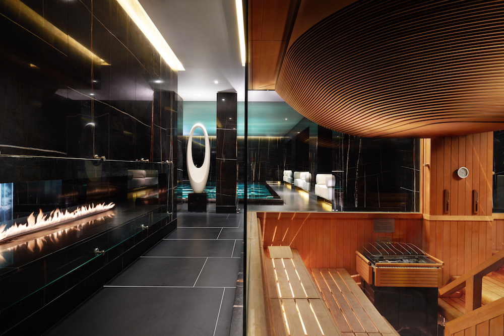 Dark spa with fire on the left and luxe sauna on the right.