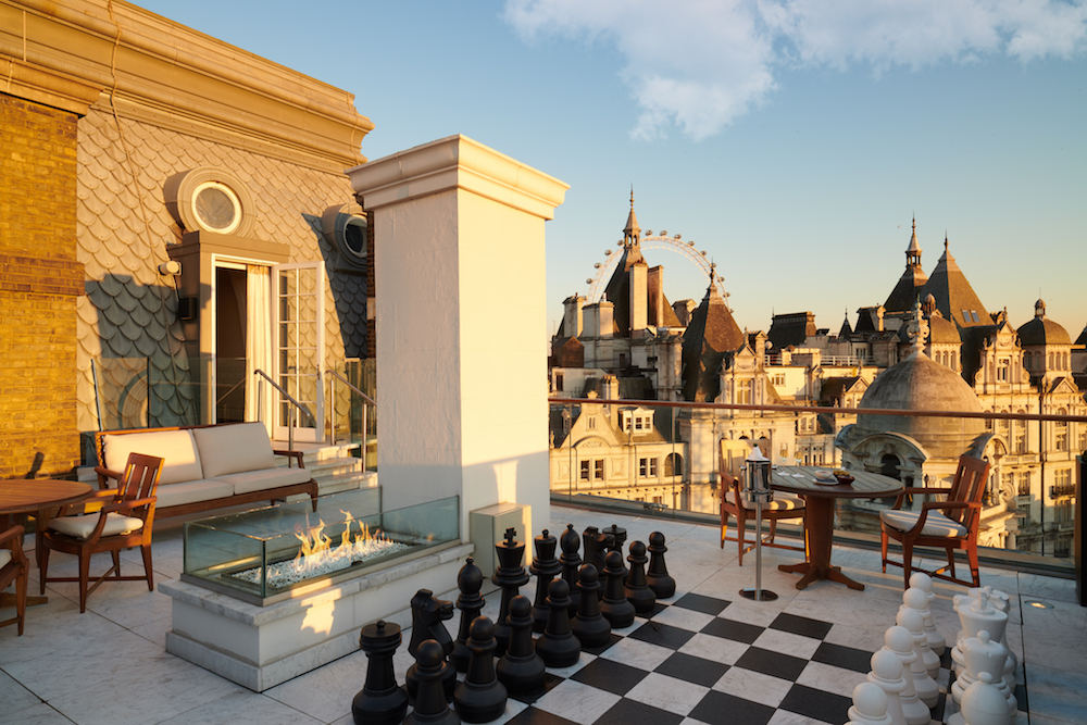 Roof terrace that has modern furniture, a large chess board and the view of the London Eye