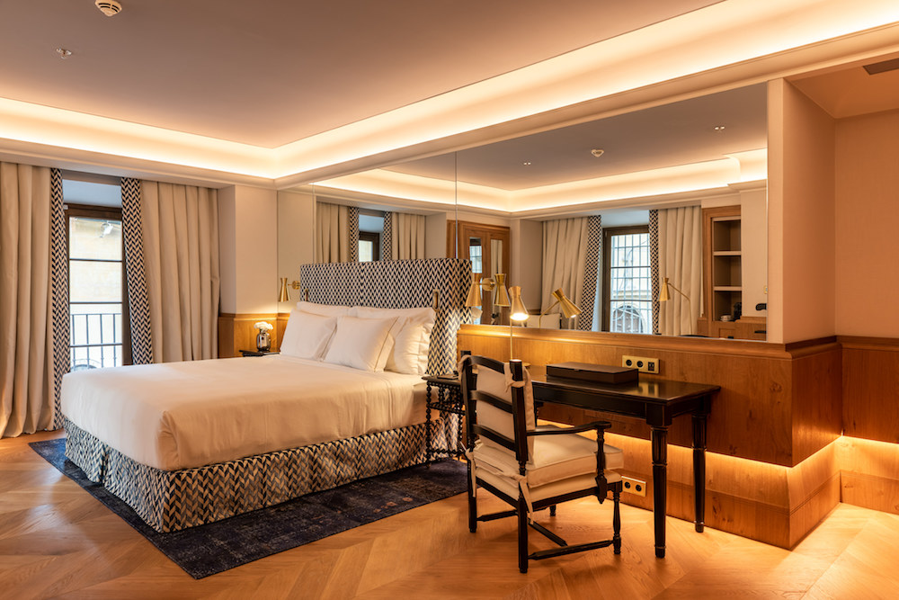 Image of the guestroom, which features blue and cream fabrics on bed, headbaord and led lighting in the ceiling