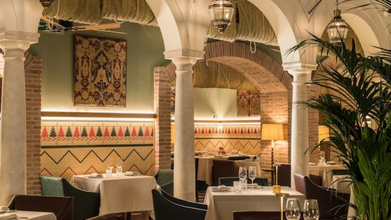 Authentic restaurant inside 18th century palace. Large pillars separate tables and rustic fabric hanging down from the ceiling adds charm and character