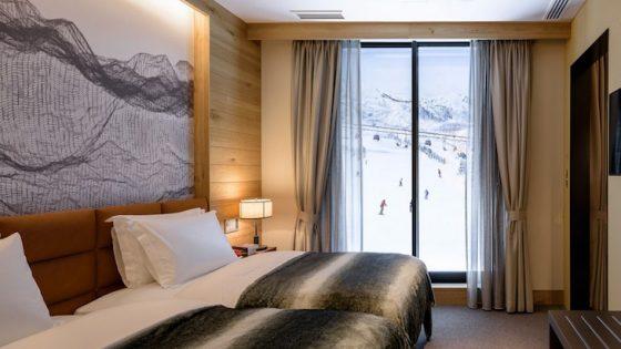 Render of luxury bedroom overlooking snowy slopes