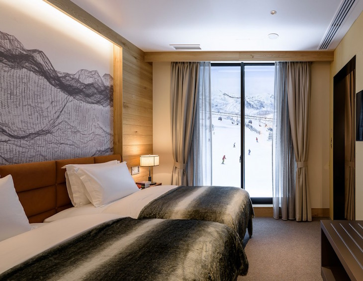 Render of luxury bedroom overlooking snowy slopes