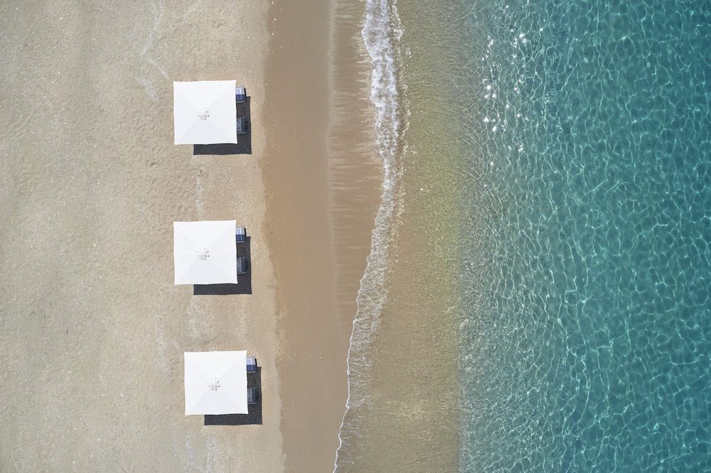 Aerial view of sea and white sunbeds