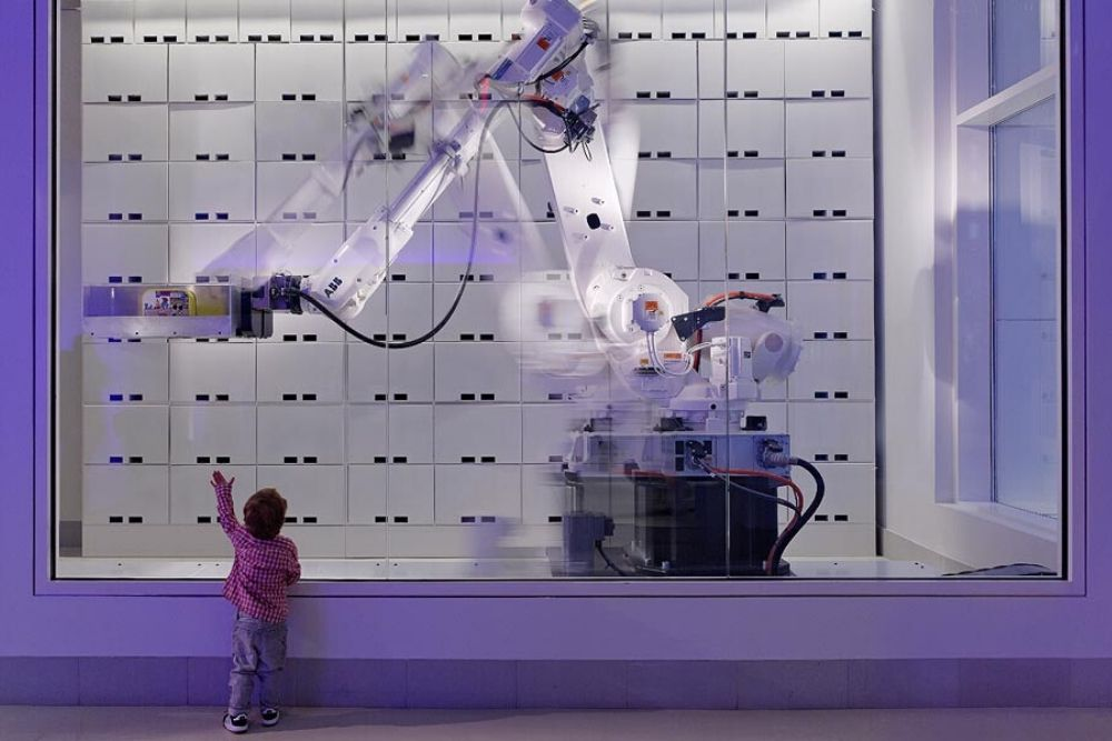 image of child reaching out to touch arm of robot