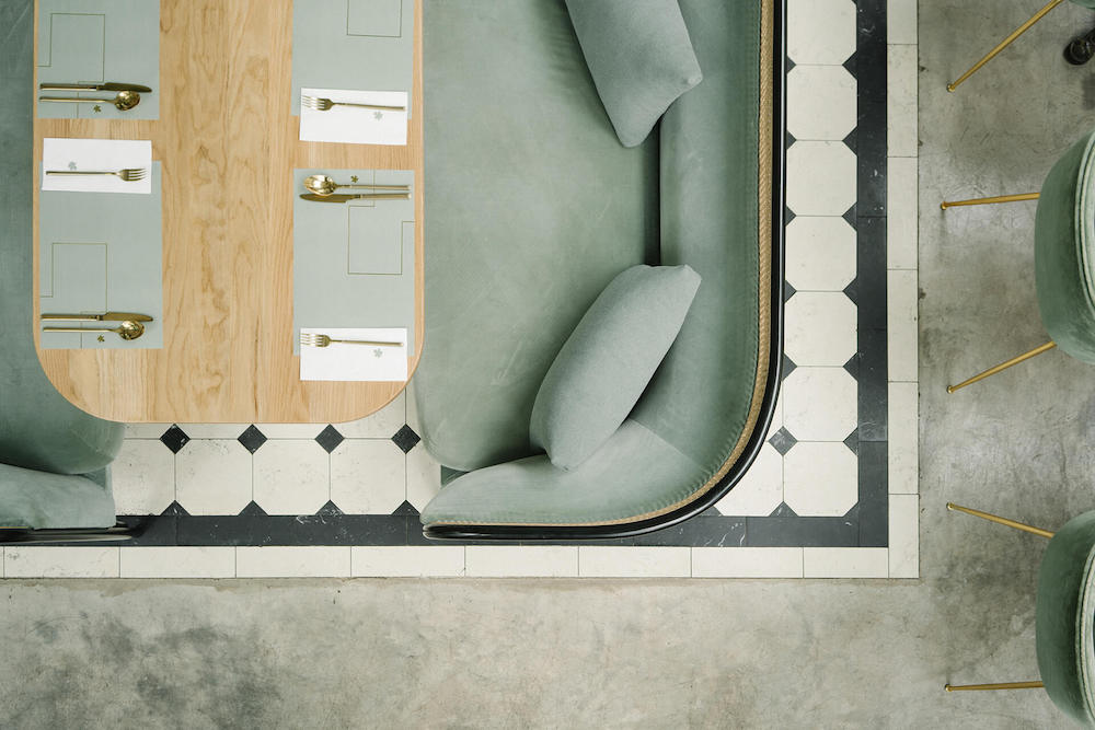 birdseye view of green sofa and cutlery