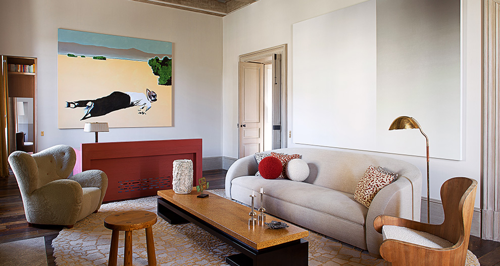 Room with interesting pieces of shaped furniture and art with man lying dead on beach