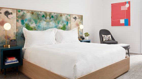 Modern guestroom with colourful accents in headboard and art