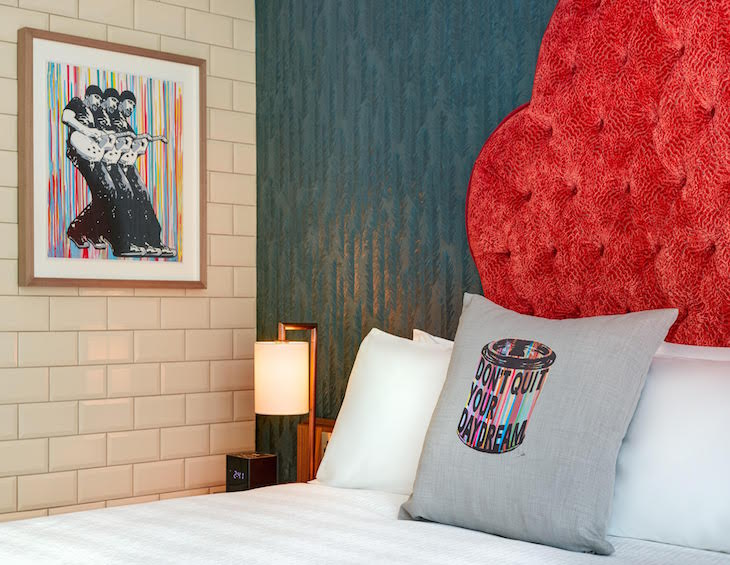 Red headboard, colourful art work and a white bed