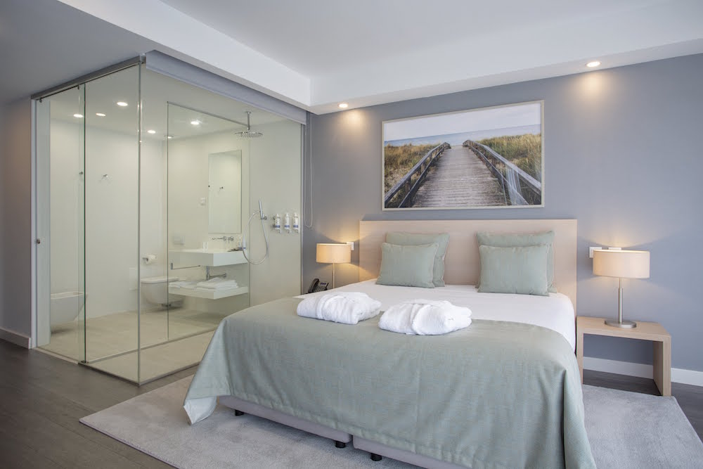 Luxe, clean and simple hotel bed with glass bathroom