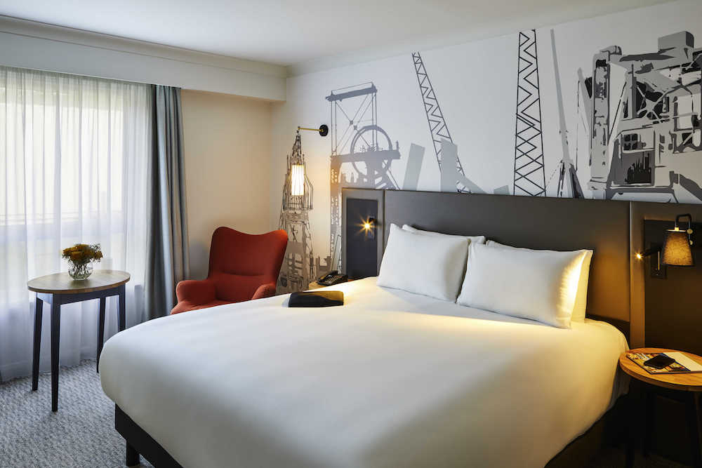 White bed, with construction inspired wallcovering