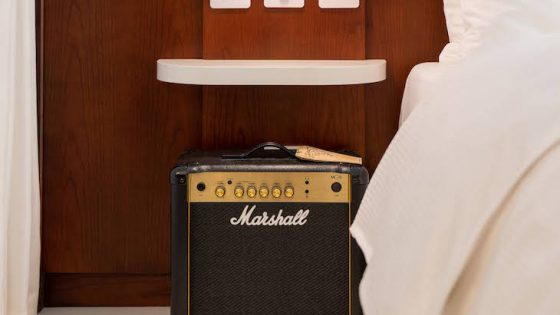 Amp by the side of white bed
