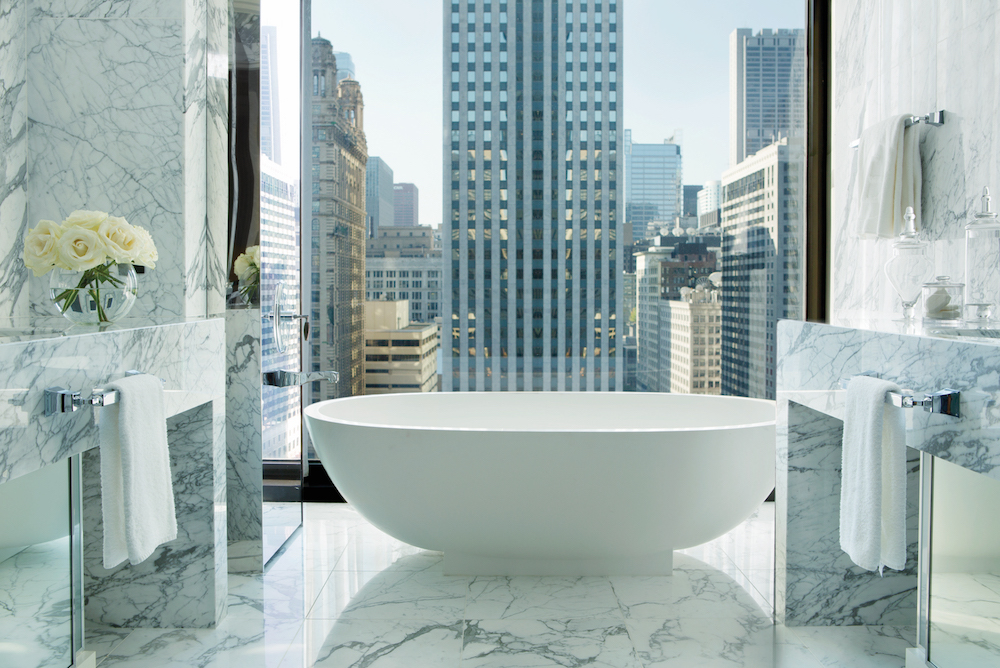 Bath in modern marble bathroom, with skyline of Chicago in the background