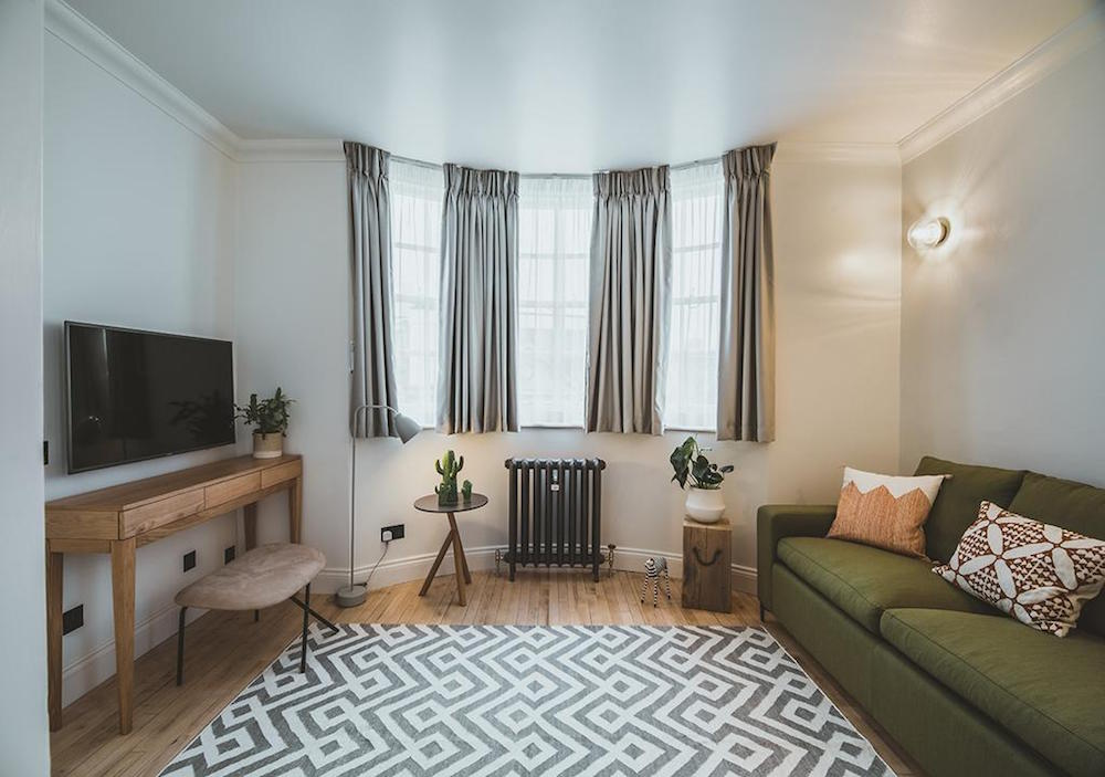 lounge area with green sofa, geometric rug and iron cast radiator