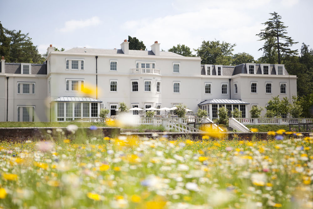 Image caption: A summertime exterior shot of Coworth Park in Ascot, which is part of Dorchester Collection