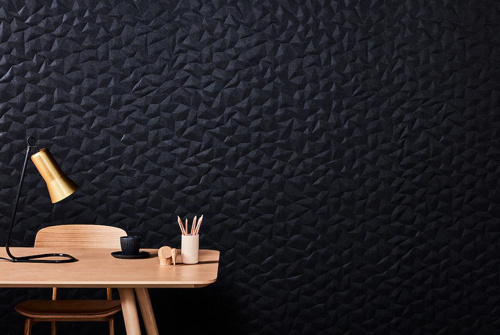 A black Japanese inspired tactile wall behind modern wooden desk setup