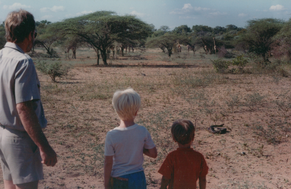 Man with two boys watching snake on safari